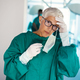Mature woman surgeon tired after an operation in hospital - PhotoDune Item for Sale