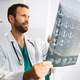 Portrait of young handsome doctor checking X-Ray in hospital - PhotoDune Item for Sale