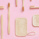 Eco friendly bamboo toothbrushes and dish washing sponges on pink background - PhotoDune Item for Sale