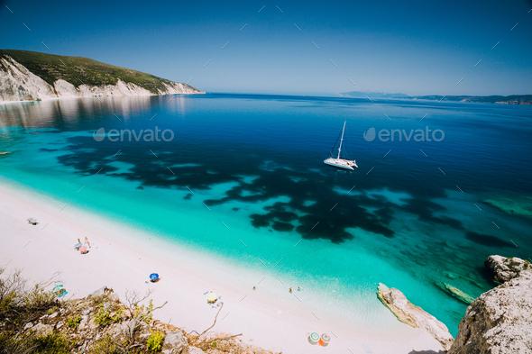 White catamaran yacht in clear blue sea water. Tourists on sandy beach near azure sea lagoon - Stock Photo - Images
