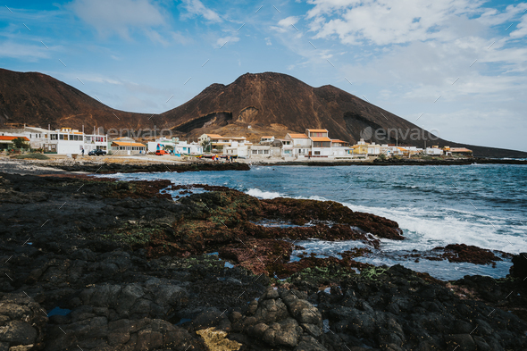 Calhau village on ocean coast in front of red colored volcanic crater. Cape Verde - Sao Vicente - Stock Photo - Images
