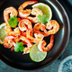Fried tiger shrimp with lime, lemon and spices on a black plate. - PhotoDune Item for Sale