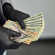 Man holding money dollars in hand in black medical gloves. - PhotoDune Item for Sale