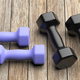Dumbbells various weight and colors on wooden floor. 3d illustration - PhotoDune Item for Sale