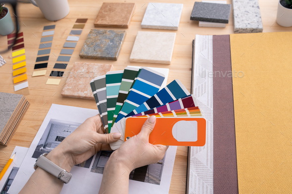Hands of young female creative designer holding color palette over table - Stock Photo - Images