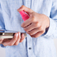 Boy in a pastel blue shirt is cleaning his phone or tablet with antiseptic in a plastic bottle - PhotoDune Item for Sale