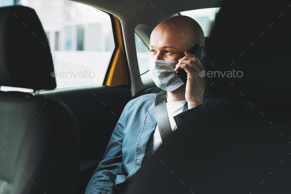 Bald man businessman in medical face mask using mobile phone inside yellow car taxi - Stock Photo - Images