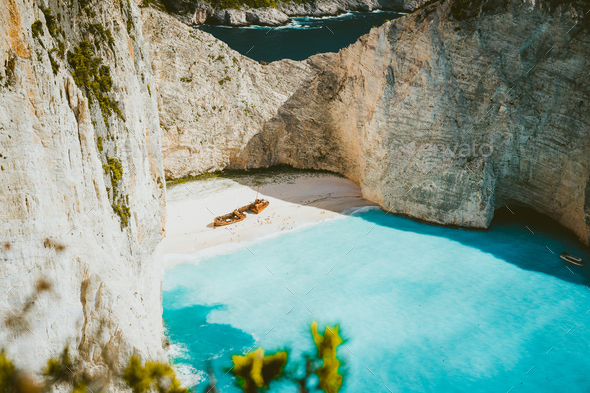Famous shipwreck of Navagio beach with turquoise blue sea water surrounded by huge white limestone - Stock Photo - Images