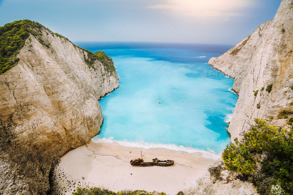 Shipwreck on Navagio beach. Azure turquoise sea water and paradise sandy beach in evening light - Stock Photo - Images