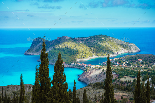 Assos village and coastline of beautiful blue sea. Cypress trees in foreground. Kefalonia island - Stock Photo - Images
