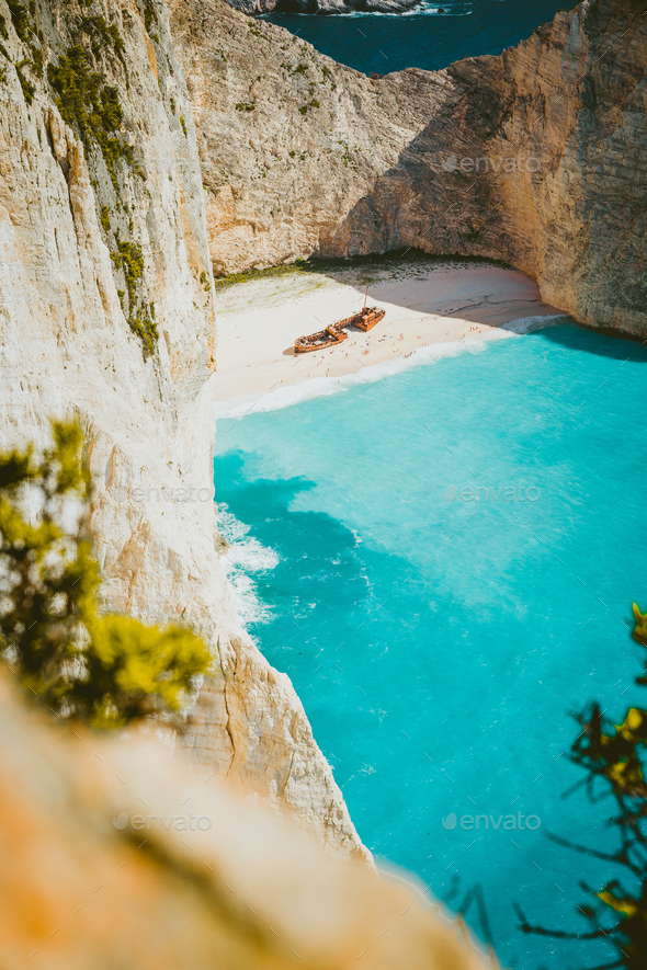 Vertical shot of shipwreck on Navagio beach with turquoise blue sea water surrounded by huge white - Stock Photo - Images