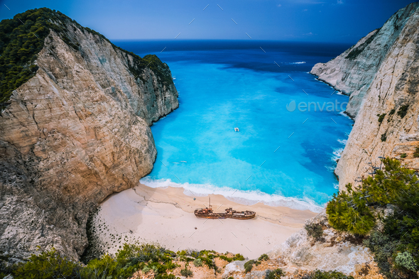 Shipwreck in Navagio beach. Azure turquoise sea water and sandy beach. Famous tourist visiting - Stock Photo - Images