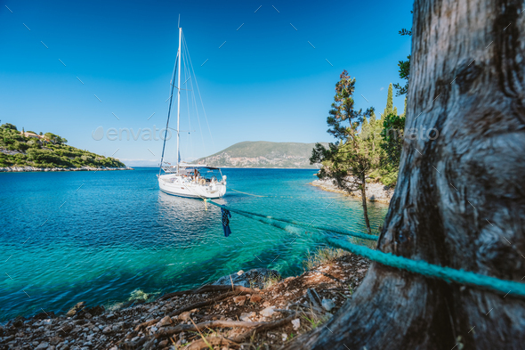 Sail boat on rope in emerald hidden lagoon among picturesque mediterranean nature Ionian Islands - Stock Photo - Images