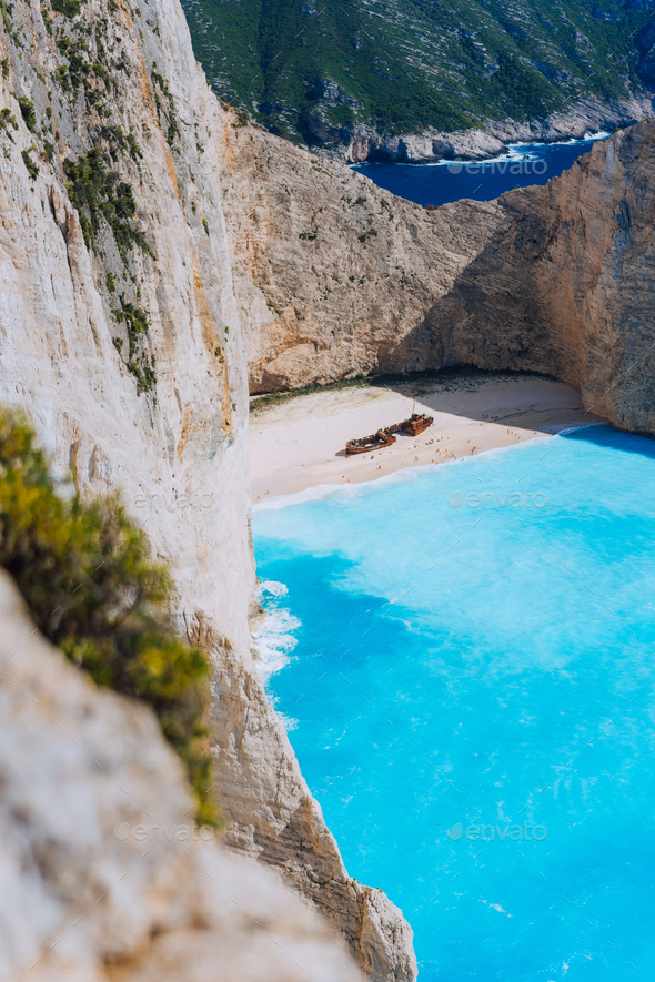 Limestone chalk colored like huge cliff rocks surrounding Navagio beach with Shipwreck and azure - Stock Photo - Images