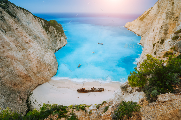 Breathtaking view of Shipwreck middle of sandy Navagio beach surrounded by azure deep turquoise sea - Stock Photo - Images