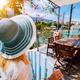 Female tourist in blue sunhat in Assos village in front of cozy veranda door admiring turquoise - PhotoDune Item for Sale