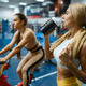 Slim girl drinks water on stationary bikes in gym - PhotoDune Item for Sale