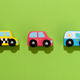 Three colorful wooden toy cars on green background - PhotoDune Item for Sale