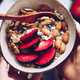Hands hold a bowl of morning granola with almond and sliced plum - PhotoDune Item for Sale