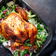 Top view of whole roasted chicken with fresh salad in black dish. - PhotoDune Item for Sale