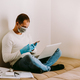 man working at home using laptop and smartphone during quarantine - PhotoDune Item for Sale