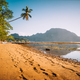 El Nido village coastline, with sandy beach and palm trees and local boats in shallow lagoon at - PhotoDune Item for Sale
