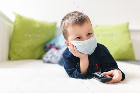 Unhappy child wearing respiratory mask as prevention against the Coronavirus Covid-19 - Stock Photo - Images