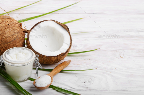 Coconut oil in airtight glass jar spoon and shell pieces on white wooden table - Stock Photo - Images