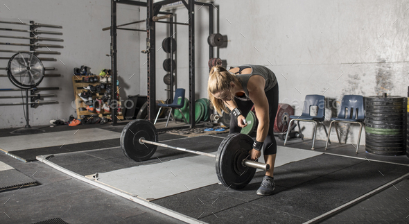 Young strong woman loading weights onto a barbell in a gym. - Stock Photo - Images