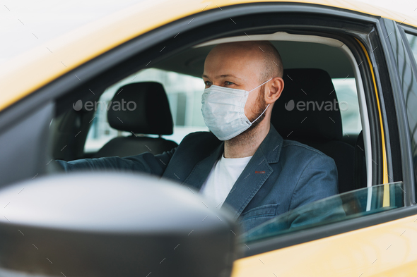 Bald man taxi driver in medical face mask inside yellow car looks - Stock Photo - Images