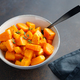 Roasted pumpkin pieces with fresh thyme in a ceramic bowl on a table. Seasonal Autumn recipe. - PhotoDune Item for Sale