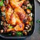 Top view of roasted chicken legs and breasts with fresh salad and mushrooms in black dish. - PhotoDune Item for Sale