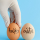 Hand in glove keeping eggs with inscription HAPPY EASTER over blue background - PhotoDune Item for Sale