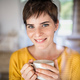Front view of young woman with coffee standing indoors at home. - PhotoDune Item for Sale