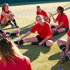 Womens Football Team Stretching Whilst Training For Soccer Match On Outdoor Astro Turf Pitch - PhotoDune Item for Sale