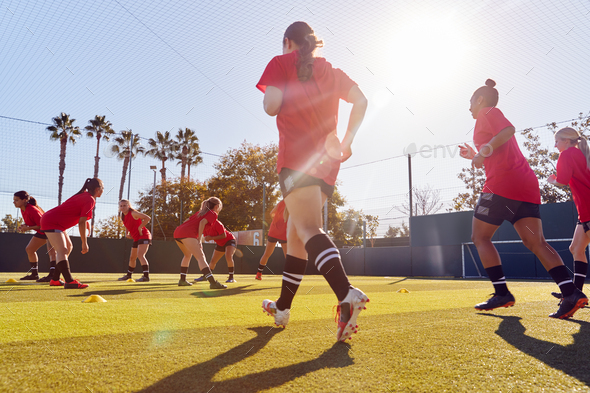Womens Football Team Run Whilst Training For Soccer Match On Outdoor Astro Turf Pitch - Stock Photo - Images