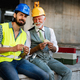 Happy mature and young engineer, architect, worker sitting at building site and resting - PhotoDune Item for Sale