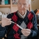 Senior Elderly Man Holding thermometer in Hands - PhotoDune Item for Sale