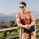 attractive muscular man smiling and posing in swim trunks outdoors - PhotoDune Item for Sale