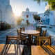 Cafe table in picturesque streets of Mykonos Chora town in famous tourist Mykonos island, Greece - PhotoDune Item for Sale
