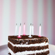 Birthday cake with burning candles on color pink background. - PhotoDune Item for Sale