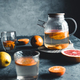 Citrus tea in a transparent teapot on a dark concrete background. Healthy drink, vegan, eco product - PhotoDune Item for Sale