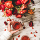 Womans hand holding glass of rose wine and ranunculus flowers - PhotoDune Item for Sale