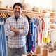 Portrait Of Male Owner Of Fashion Store Standing In Front Of Clothing On Rails - PhotoDune Item for Sale