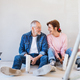 Senior couple painting walls in new home, resting. Relocation concept - PhotoDune Item for Sale