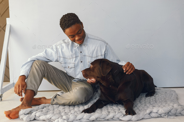 Handsome black man sitting on a blue background with a dog
