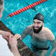 Smiling swimmer listening to coach - PhotoDune Item for Sale