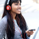 smiling young Indian woman sitting outside with mobile phone and headphones - PhotoDune Item for Sale