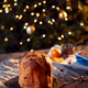 Traditional Christmas Panettone On Table Set For Festive Meal With Tree Lights In Background - PhotoDune Item for Sale