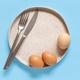 Plate, eggs, fork and knife over light blue background - PhotoDune Item for Sale